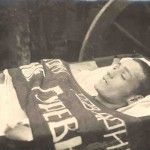 A dead Party member lies in his coffin, a banner across his chest instead of flowers.