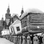 Red Army soldiers holding an inflatable Kolkhoz village in a Red Square parade. Little do they know that Captain Korolev is about to be involved in a nearby shoot-out that will send those balloon soaring skywards.